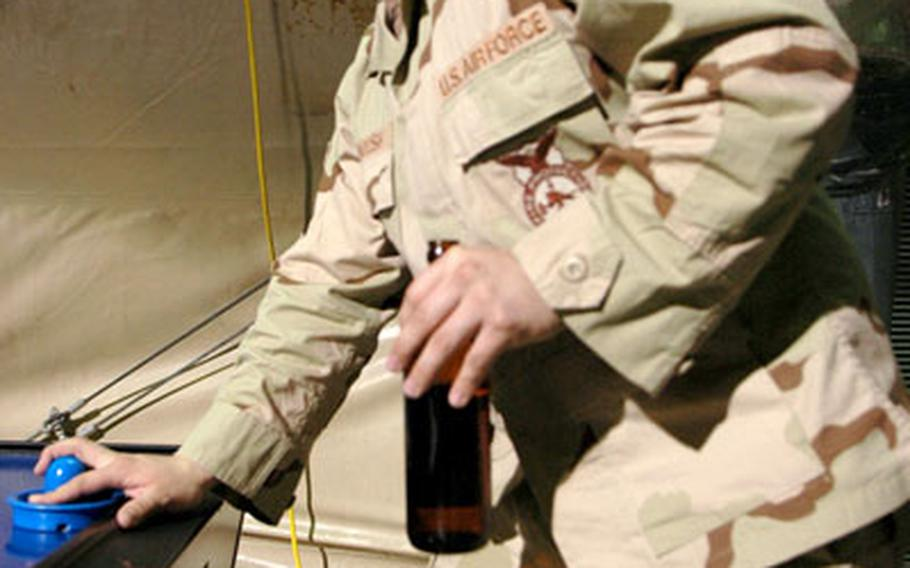 Airman 1st Class Andrew McIntosh, 21, enjoys a beer while lamenting that some of his Army brethren can't do the same.