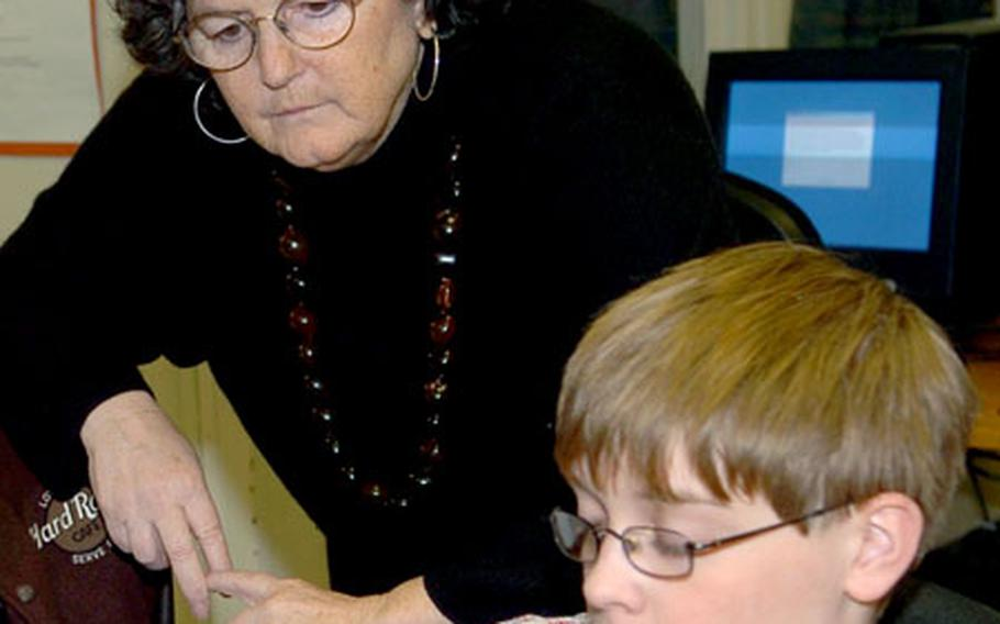 Ellen Minette, principal of Heidelberg Middle School in Germany, reviews work being done by seventh-grader Tommy Johnson in the school's library on Tuesday.