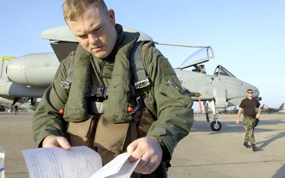 1st Lt. Keith Bonser checks maintenance forms before a Cope Tiger '06 mission on the ramp at Korat Royal Air Force Base on Wednesday. Bonser is an A-10 pilot from the 25th Fighter Squadron from Osan Air Base.