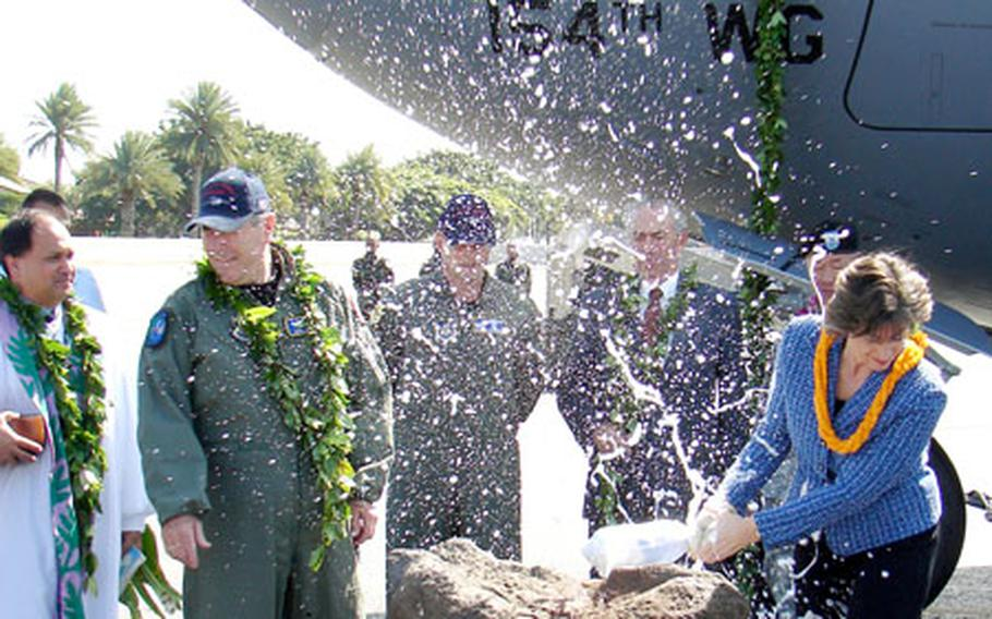 Gen. Paul V. Hester, commander, Pacific Air Forces, and Hawaii Gov. Linda Lingle react as Lingle christens PACAF's first C-17 at Hickam Air Force Base.