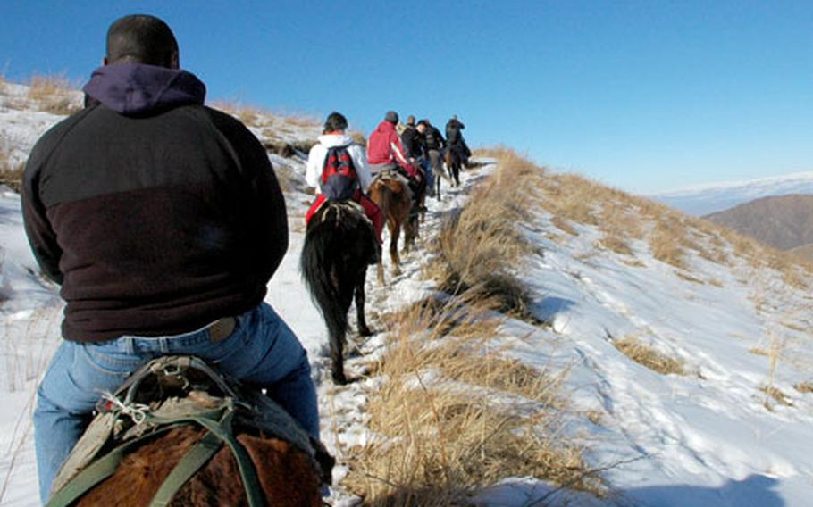 A group of U.S. airmen ride through the snow-covered mountains during an outing on a day off from work. The airmen are deployed to Manas Air Base in Kyrgyzstan.