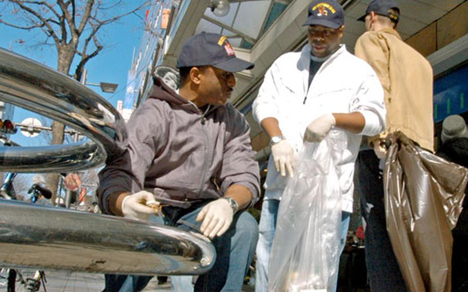 Petty Officers 3rd Class Hamzza Moore and Jarvis Robertson of the USS Kitty Hawk were part of a 90-volunteer clean-up effort in Yokosuka, Japan, on Friday.