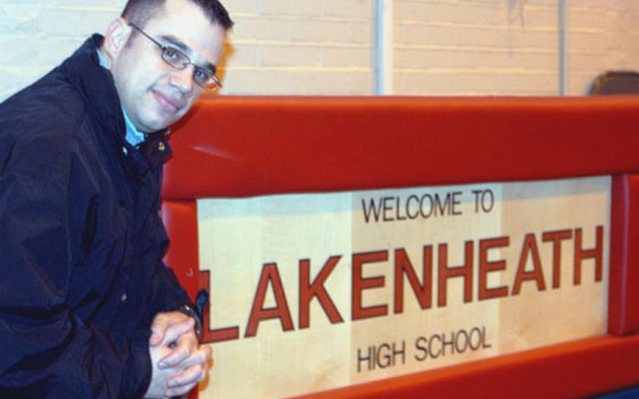 Staff Sgt. Michael Falvo kneels next to the scorer's table at Lakenheath High School. After three years as the play-by-play announcer for the Lancers, Falvo is leaving to work for the American Forces Network in Portugal.