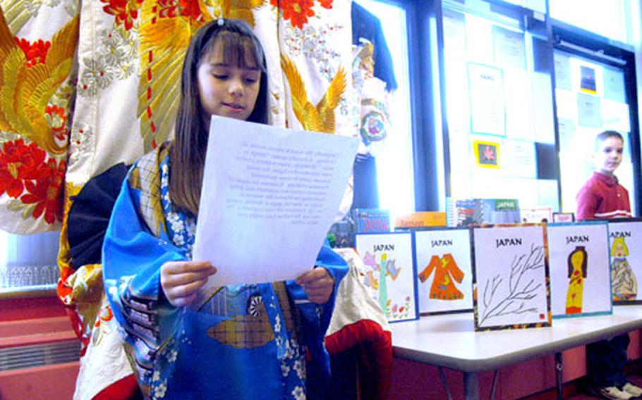 Alyssa Carney, 8, reads her presentation about kimonos, the traditional form of Japanese dress like the one she's wearing, last week at the Lakenheath Elementary School. Hanging behind Carney is an adult-sized version of the decorative robe.