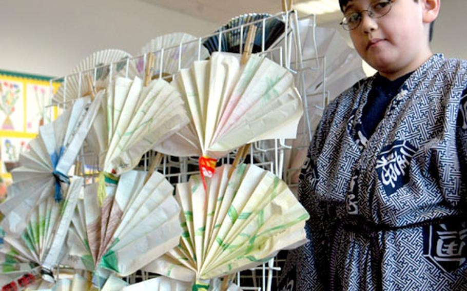 Scott Lovett, 8, wearing traditional Japanese clothing, shows off Japanese fans, some authentic and some made by members of a third-grade class.