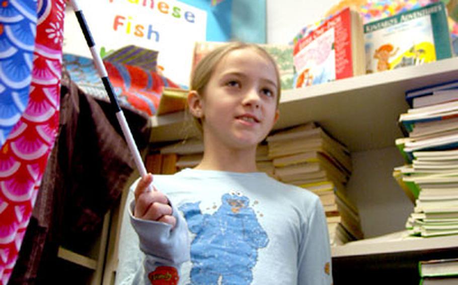 Holding a Japanese fish kite, Gracie Parrott, 8, talks about the decorative wind socks often seen around Japan.
