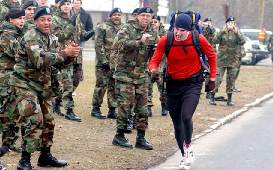 Spc. Jacob Truex, carrying a 40-pound backpack, is cheered by fellow soldiers Tuesday as he attempts to set the Guinness World Record in the one-mile and five-kilometer backpack runs at Fliegerhorst Casern in Hanau, Germany.