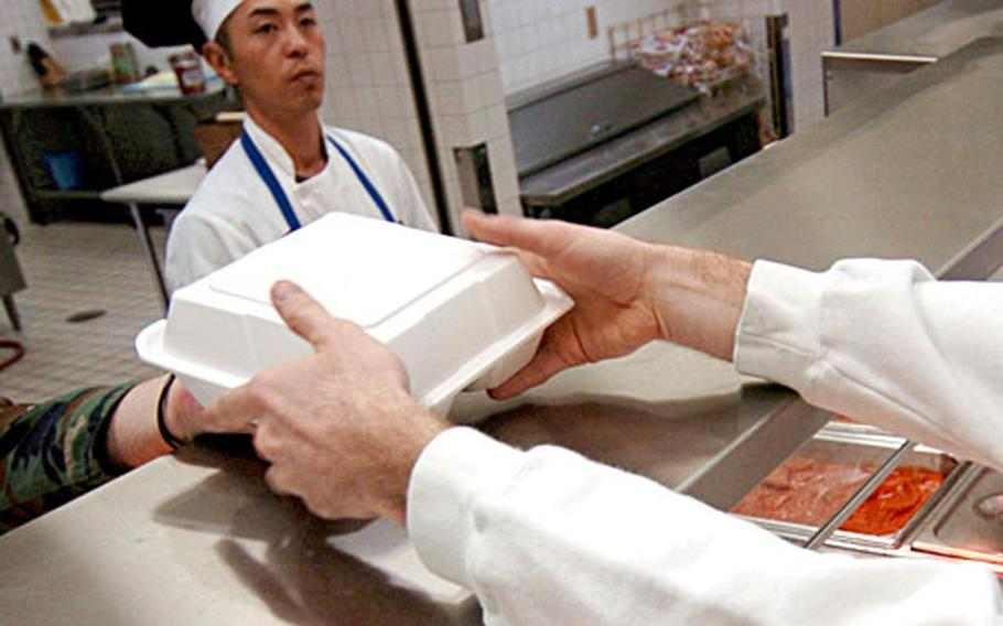 An airman picks up lunch recently in the Samurai Cafe at Yokota Air Base, Japan. The dining facility was named best in Pacific Air Forces last fall and is now in the running for the 2006 Hennessy Award, the service's top honor.