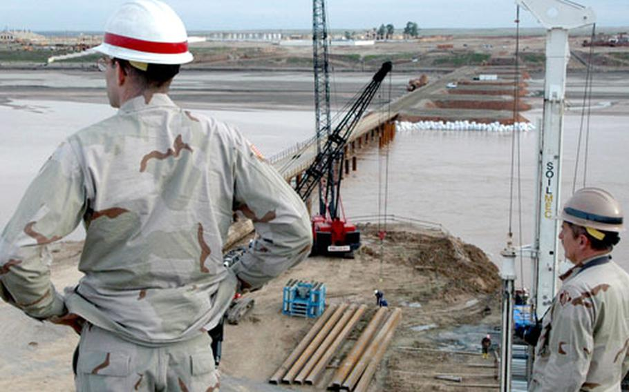 Col. Christopher Toomey surveys a bridge built by the U.S. Army Corps of Engineers to span the Oxus River. The project aims to link Afghanistan and Tajikistan, providing a valuable trade route.