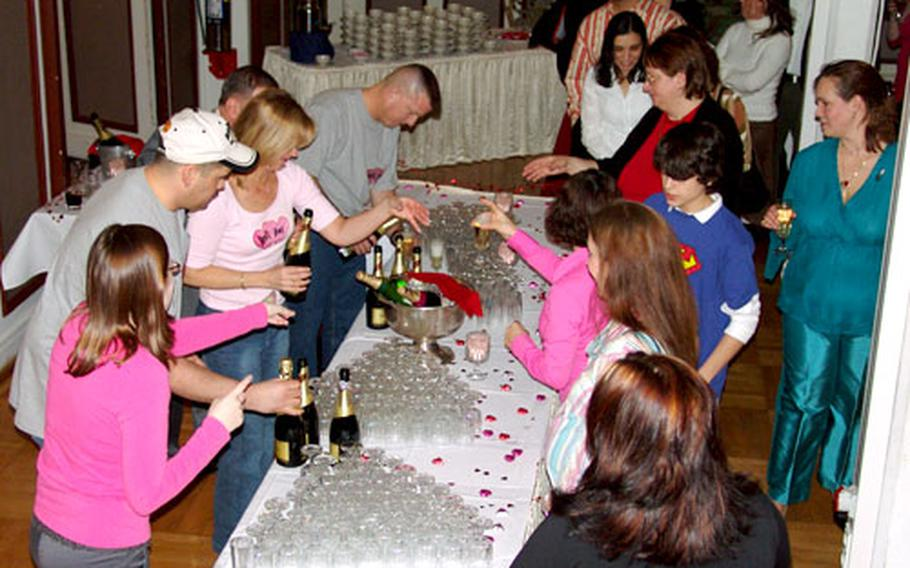 A line forms at the champagne table as Baumholder, Germany, officers and spouses celebrate Valentine's Day with a party. About 170 people packed into the ballroom of the Rhinelander, the base club.
