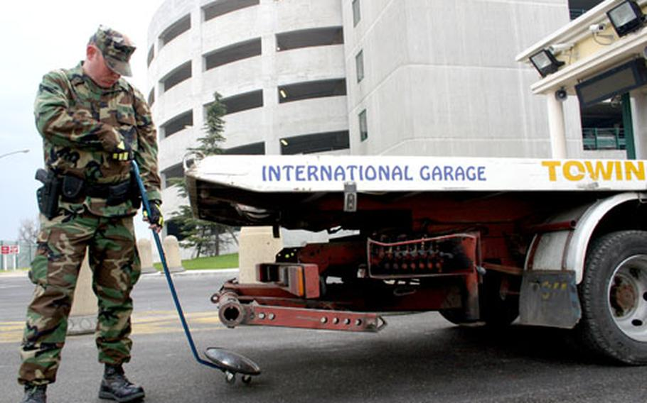Petty Officer 3rd Class Christopher Darling, 24, scans the undercarriage of a tow truck at Naval Support Activity Naples, Italy. The number of security personnel has steadily decreased over the past few years.