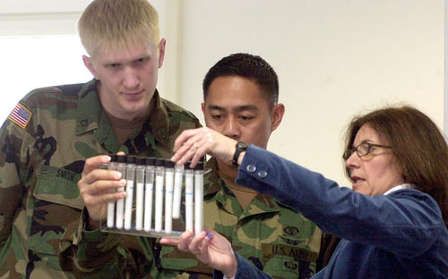 """Pfc. Steven Smith, left, and Staff Sgt. Dennis Ladrillono check out the sugar-content display at Baumholder's first Women's Health Fair. Most people say """"Gross!"""" when they see how much fat or sugar is in processed foods such as potato chips and soft drinks, said Cathy Douglas, right."""
