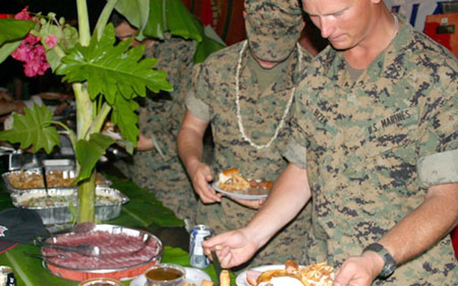 Marines with the 31st Marine Expeditionary Unit fill their plates during the barbecue party.