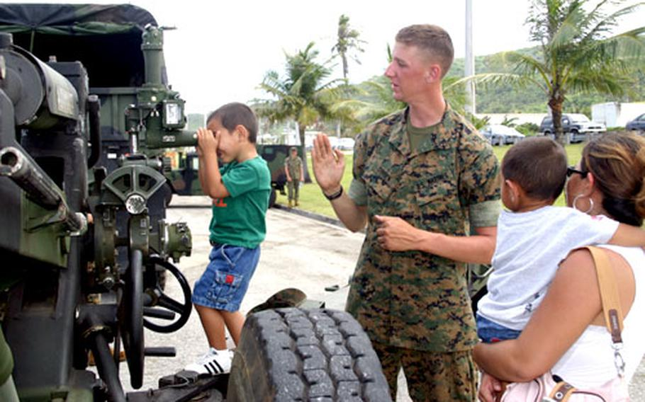 Pfc. Daniel O'Brien, of Kilo Battery 312, explains the workings of the unit's M-198 medium towed howitzer to Guam resident Darla Flores as she holds son Tyler, 1, and her son Thaddeus, 4, looks through the weapon's scope during Marine Day at Asan Beach Park, Guam, on Feb. 8.