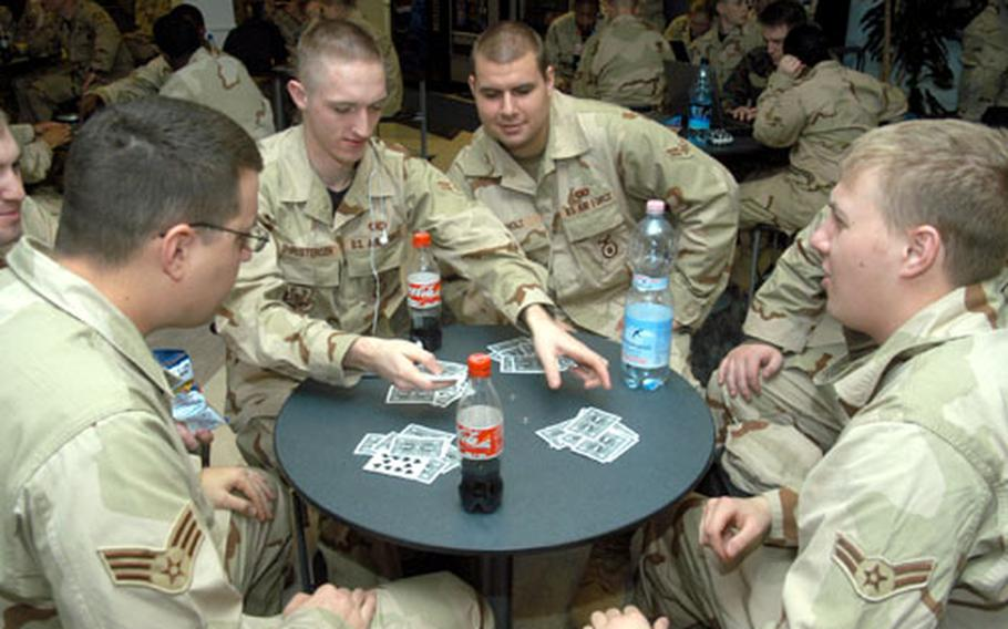 Airmen from the 31st Security Forces Squadron out of Aviano Air Base in Italy, play spades as they wait for a flight out of the RAF Mildenhall passenger terminal. On Thursday, the terminal became a hub for Air Force security forces deploying to various locations in the Central Command.