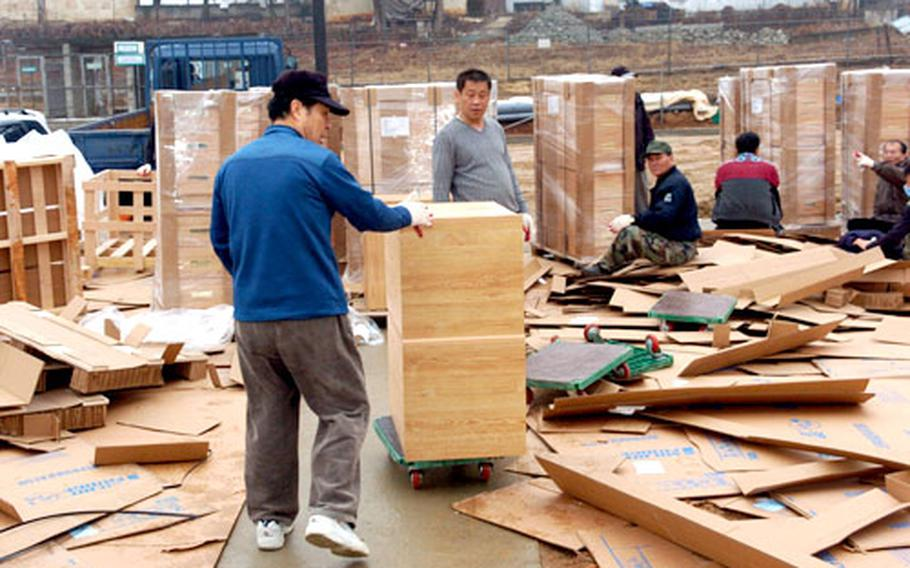 At Camp Humphreys in Pyeongtaek, South Korea, earlier this week, workers unload furniture that will go into barracks at the newly built twin six-story barracks-dining hall complex in the post's Zoeckler Station area.