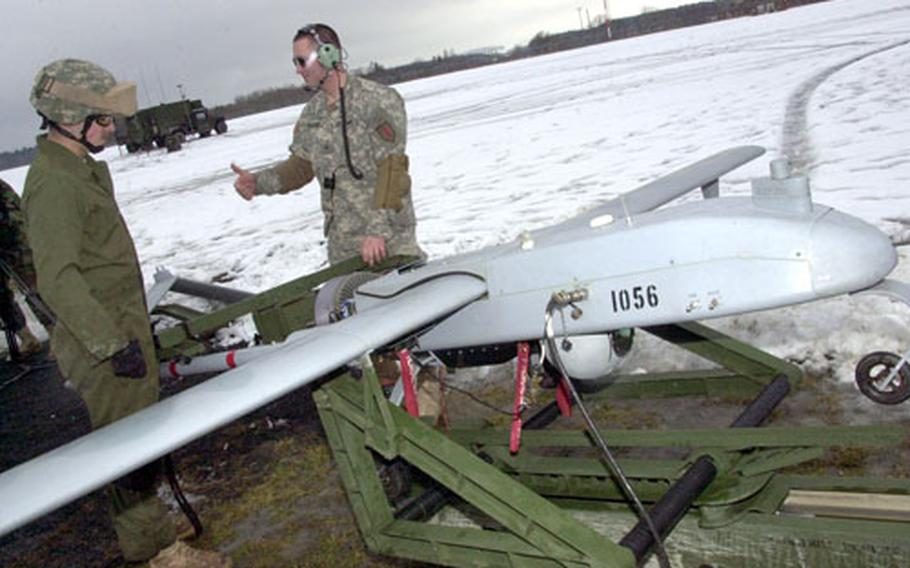 Spc. Robert Hartung, left, and Cpl. Jonathan Williams, both of Company C, 101st Military Intelligence Battalion, roll a Shadow Unmanned Aerial Vehicle onto its launch ramp at Vilseck Forward Arming and Refueling Point on Thursday.