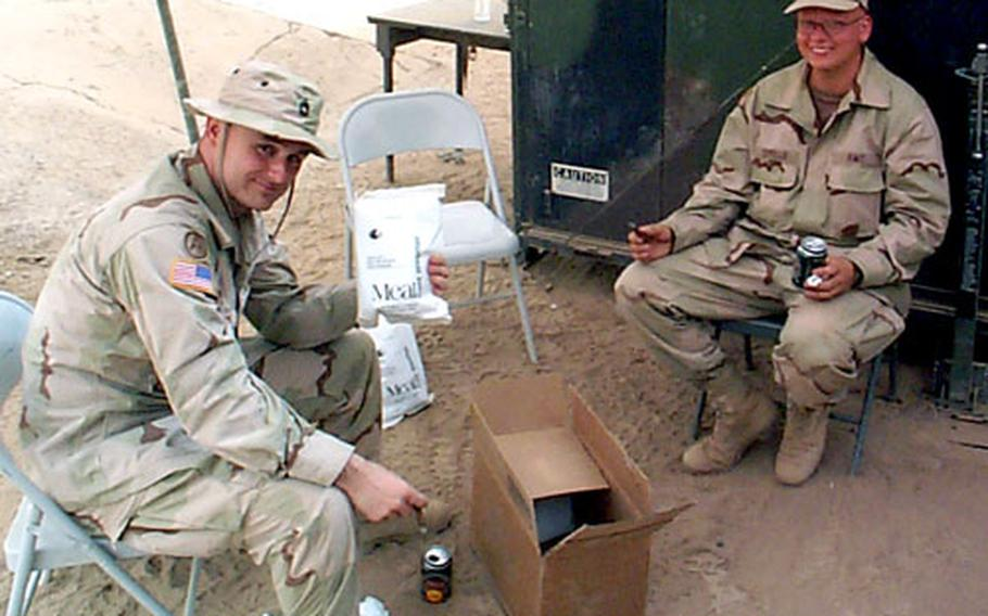 Sam Newland, left, of the Natick Soldier Center tests a Meal, Cold Weather (MCW) ration in 115-degree weather in Iraq in June 2003. New menus for the MCW and Food Packet, Long Range Patrol rations have been developed with the help of solider taste-testers.