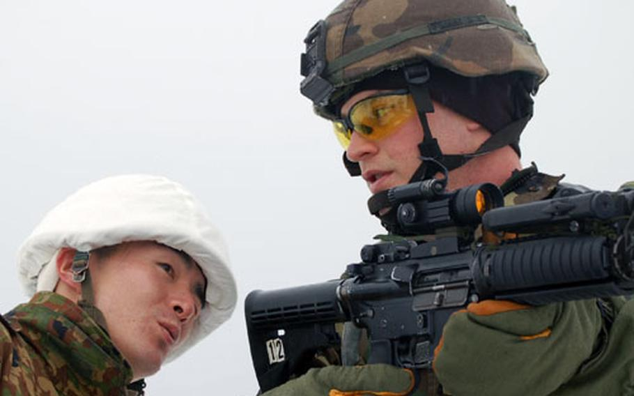 Sgt. Timothy Sides shows the correct technique for close-quarters marksmanship as Sgt. 1st Class Shuji Ohsaka of the Japan Ground Self Defense Force pays close attention during Exercise North Wind '06 in Camp Iwate, Japan.