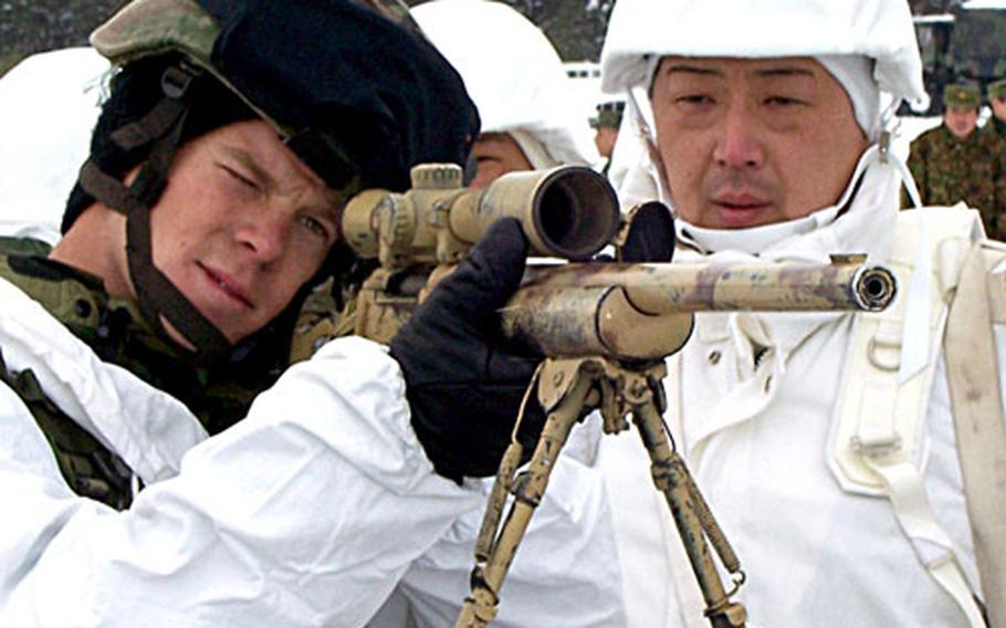 Staff Sgt. Jason Payton peers through a scope mounted on an M-24 sniper rifle as he shows Sgt. 1st Class Yoshio Harako of the Japan Ground Self Defense Force the proper shooting form during Exercise North Wind '06 in Camp Iwate, Japan.