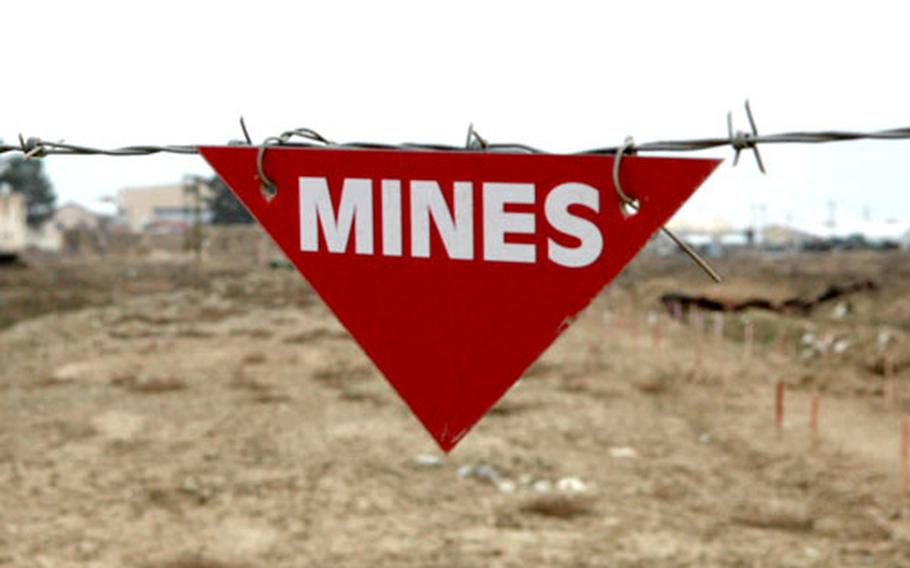 Red flags mark areas on Bagram Air Base, Afghanistan, where members of a Polish demining team search for mines and old ordnance used as bombs. As many as 20 million mines are scattered across the country.