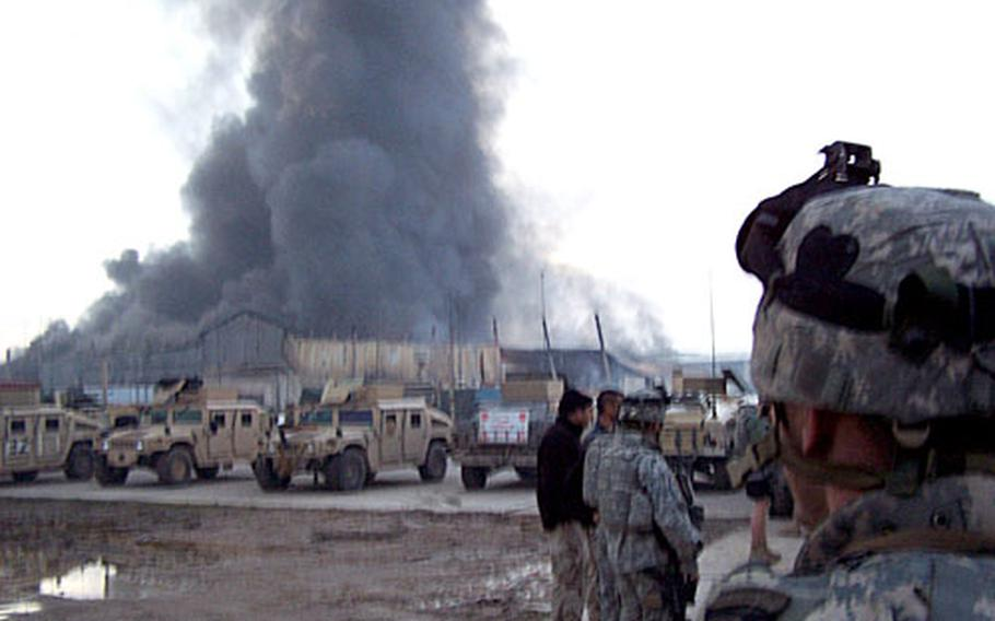 Soldiers from Company B, 1st Battalion, 502nd Infantry, 2nd Brigade Combat Team, 101st Airborne Division, watch as their main building at FOB Yusafiyah goes up in smoke Feb. 5.