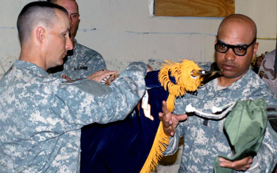 Lt. Col. Chris Toner, commander of the 2nd Battalion, 87th Infantry Regiment, and Command Sgt. Maj. Jose Vega unfurl the colors of the battalion during the transfer of authority ceremony Sunday at Forward Operating Base Orgun-E.