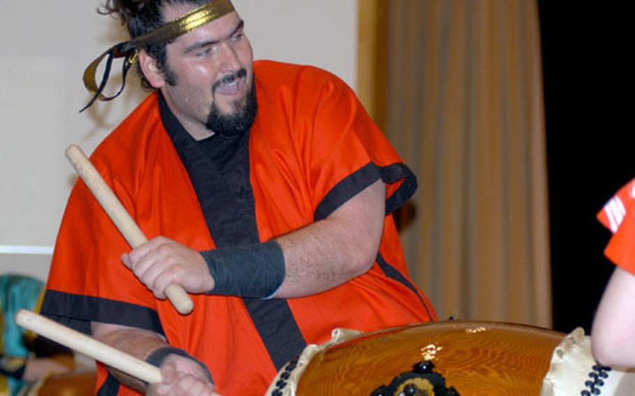 David Wray, a member of the Dragon Eagle taiko drum team at Misawa Air Base, Japan, beats a taiko drum with bachi sticks on Saturday during the group's concert on base. The American taiko drum group celebrated its seventh anniversary Saturday.