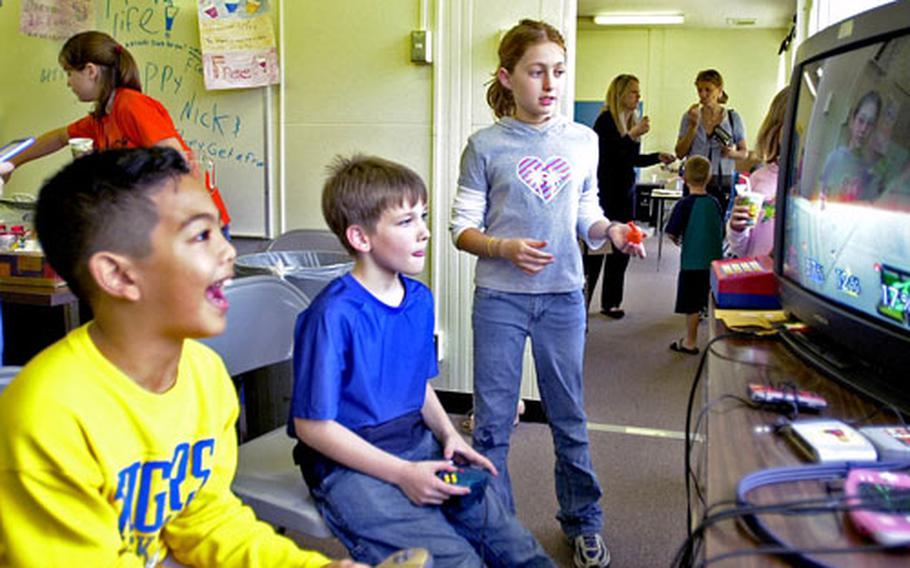 """Isabel Hagopian, right, watches as Ricky Arellano, left, and Peter Trusty play video games at her """"business"""" at Stearley Heights Elementary School on Kadena Air Base. The third- and fourth-grade multi-age classes at the school currently are taking part in a """"mini-society"""" economics program in which they create their own businesses and run them."""