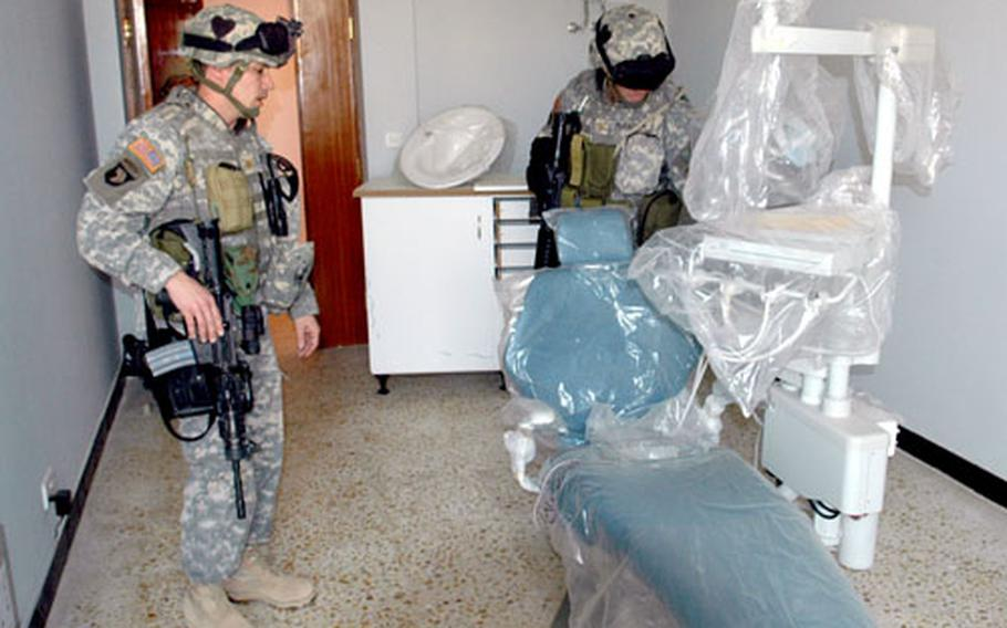 U.S. soldiers inspect a nearly completed medical clinic in Mahmudiyah, which a private nongovernmental organization may run until the Iraqis are ready to take over active management.