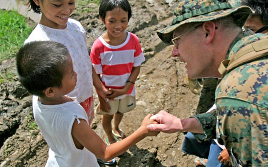 Gunnery Sgt. Craig J. Fried of 31st Marine Expeditionary Unit spends a few moments Sunday with children from the area around the devestated Philippine town of Guinsahugon. Guinsahugon was destroyed Feb. 17 by a mudslide from a nearby mountain.