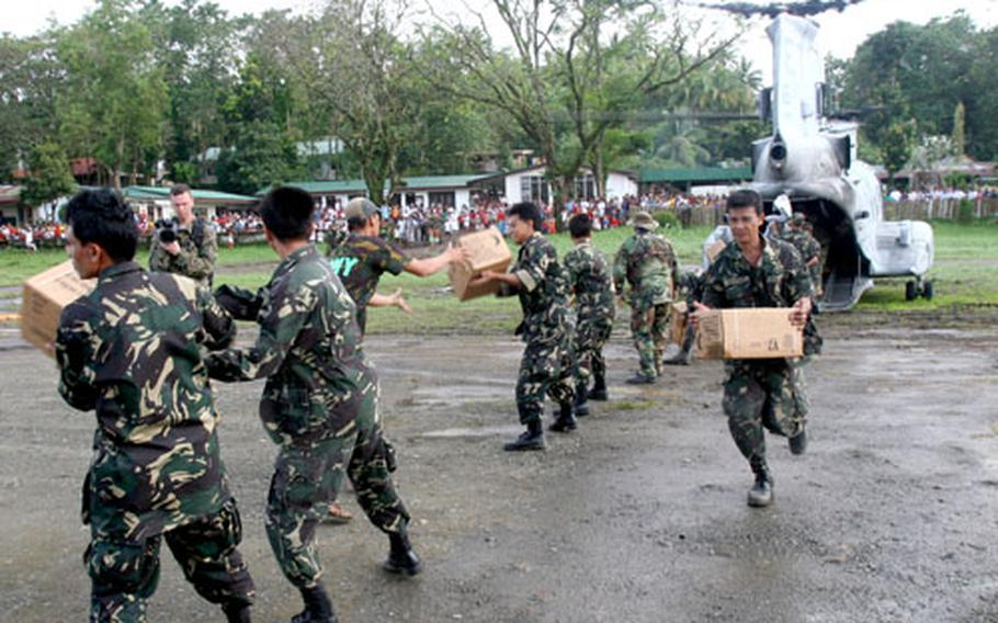 Members of the Philippine Army help U.S. Marines and sailors unload supplies from a CH-46E Sea Knight helicopter as part of the relief effort being conducted in the southern part of the island of Leyte.