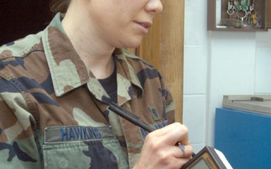 Staff Sgt. Christine Hawkins labels an air sampling cassette before obtaining an air sample at the 100th Maintenance Squadron shop.