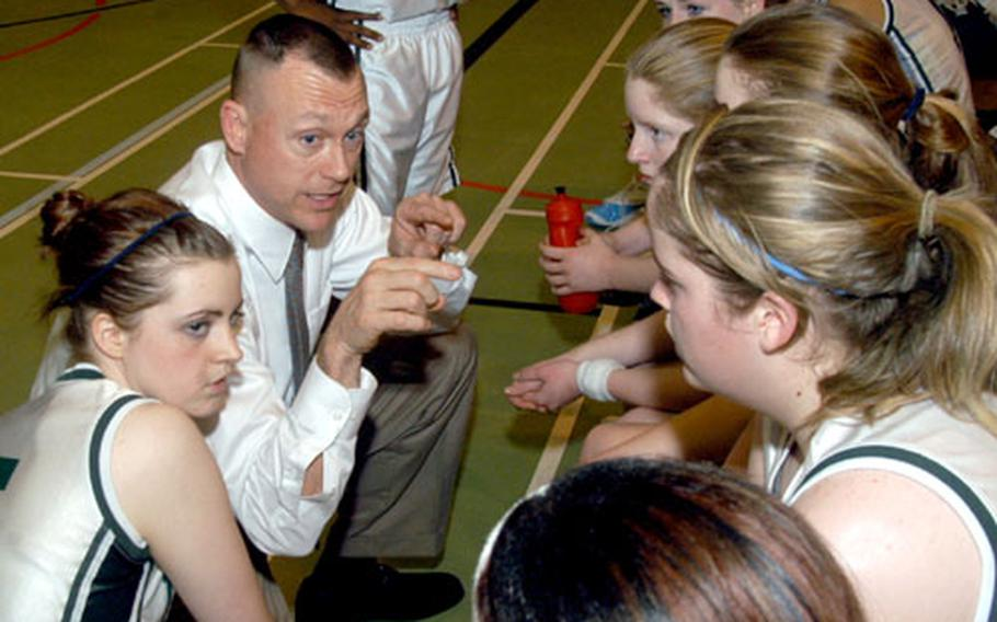 Alconbury coach Ron Davis goes over a game plan with his Lady Dragon players during a game against London Central.