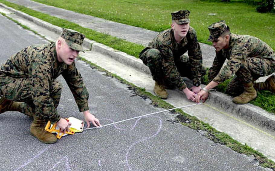 From left, Lance Cpls. Christopher Taylor and Paul Johnston and Cpl. Daniel Martinez take measurements of a mock fatal vehicle accident scene. The Marines are all military policemen and are taking part in an accident investigators course on Camp Foster, Okinawa.