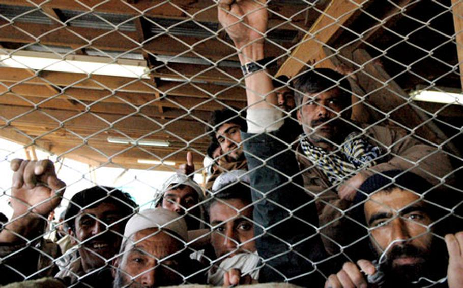 Men seeking work clutch at a chain-link fence dividing them from Bagram Air Base.