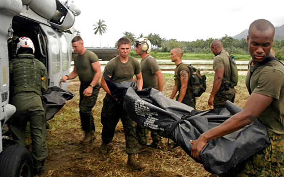 Marines with the 31st Marine Expeditionary Unit unload an HS-60S helicopter from Helicopter Sea Combat Squadron 25. The helo landed near the buried village of Guinsaugon to deliver supplies and equipment from the Sasebo, Japan-based USS Harpers Ferry.