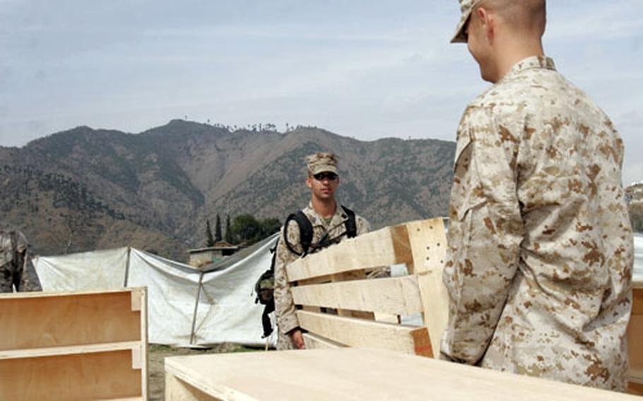 Seaman Jonathan F. Casale, left, and Lance Cpl. Keith A. Post unload furniture at the Seran Sialkot Tent Village in Daryal, Pakistan. Servicemembers from the Okinawa-based Combined Medical Relief Team 3 recently built and donated benches, shelves, computer tables, exam tables and floor decking to a clinic in the village.