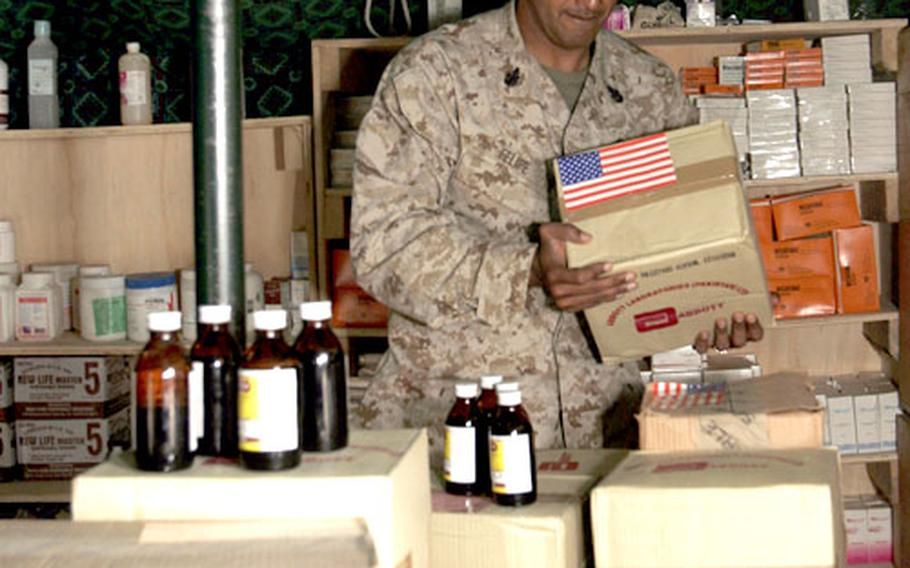 Navy Senior Chief Petty Officer Rafael D. Felipe carries a box of medicine into the pharmacy at the Seran Sialkot Tent Village recently in Daryal, Pakistan. Okinawa-based Combined Medical Relief Team 3 donated 900 bottles of much needed liquid medication to a clinic there. Felipe is the staff noncommissioned officer in charge of CMRT-3.