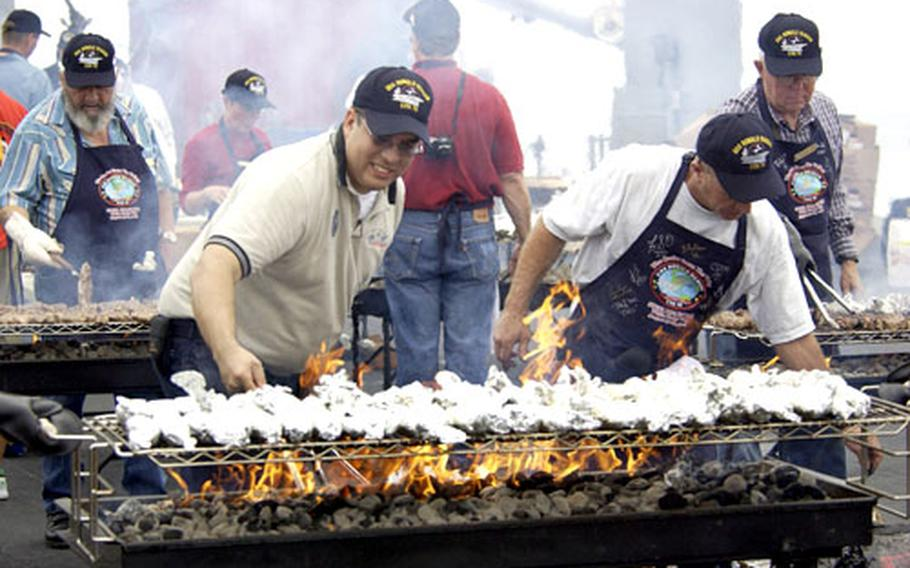 """Volunteers prepare steaks for the crew aboard the USS Ronald Reagan during a """"steel beach picnic"""" in August. The USS Reagan, which is on its maiden voyage, has all the amenities to make sailors feel right at home while on the ship."""