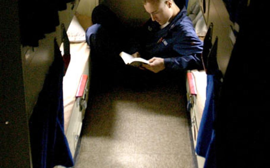Petty Officer 3rd Class Les Sheffield, from Sweetwater Texas, reads a novel while he relaxes in between two racks after a long day of work aboard the USS Ronald Reagan, which is on its maiden voyage.