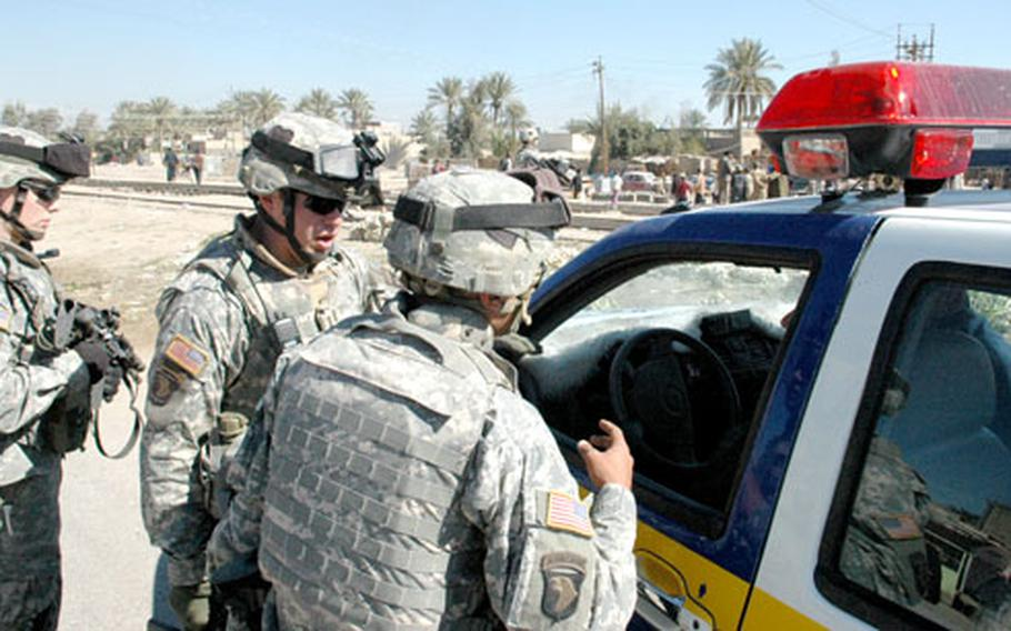U.S troops instruct Iraqi police officers in Mahmudiya, Iraq, to enforce the nationwide curfew. The police quickly issued orders through a loundspeaker for locals to get off the street.