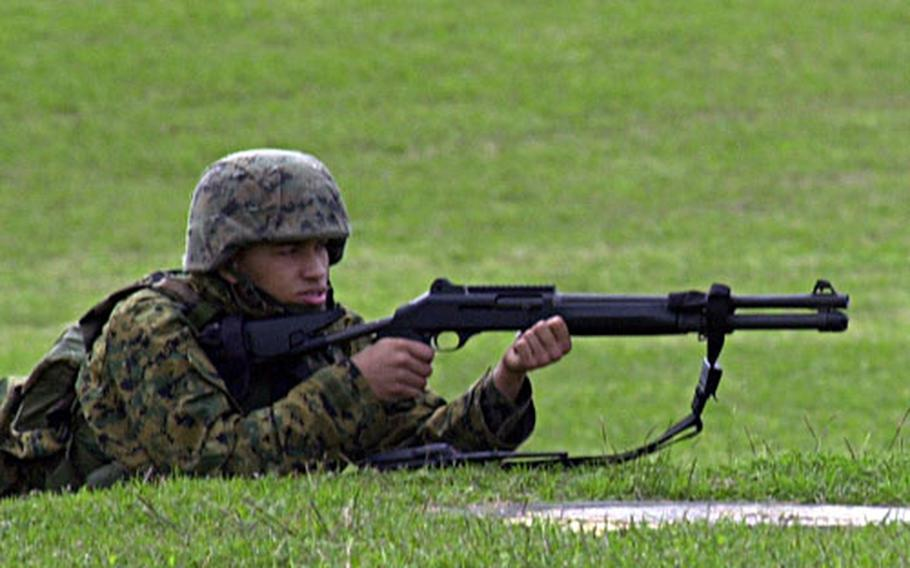 An auxiliary force Marine takes up a defensive position outside Kinser Elementary School on Saturday during a force protection drill.