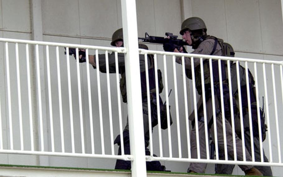 Marines of the Provost Marshal's Office Special Reaction Team respond Saturday to a mock scenario in which two men took hostages at Kinser Elementary School on Okinawa, during the force protection exercise Constant Vigilance 06-1.