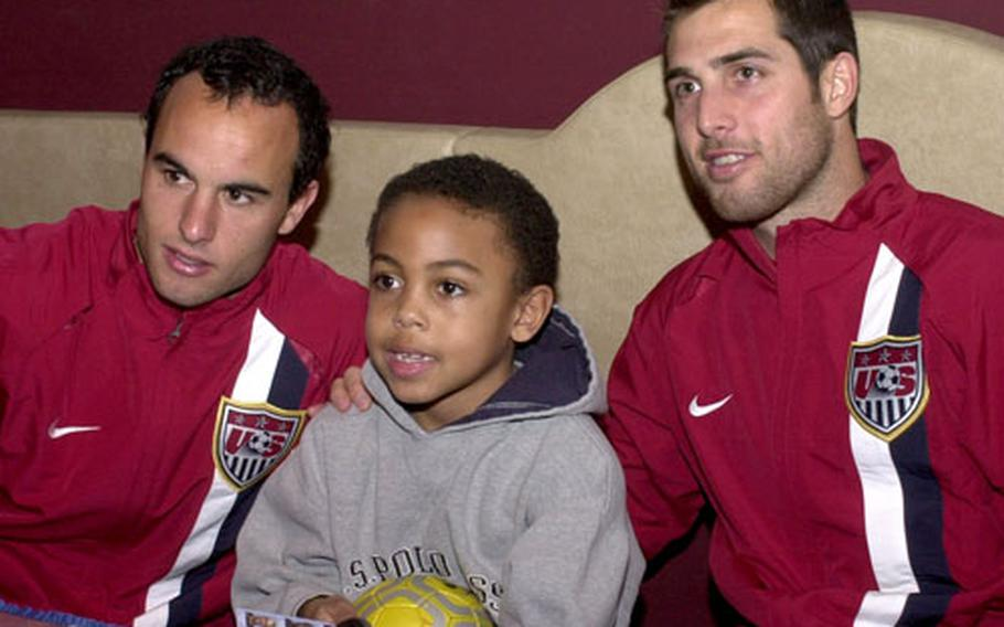 Landon Donovan, left, and Carlos Bocanegra, of the U.S. men's soccer team, pose with Weston McKennie, 7, at Ramstein Air Base, Germany, on Monday. The U.S. plays Poland in a friendly match at Fritz-Walter Stadium in Kaiserslautern, Germany, on Wednesday.