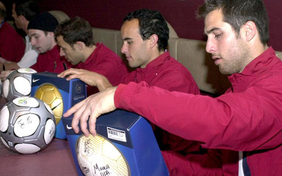 U.S. soccer team members sign autographs at the enlisted club at Ramstein Air Base, Germany, on Monday.