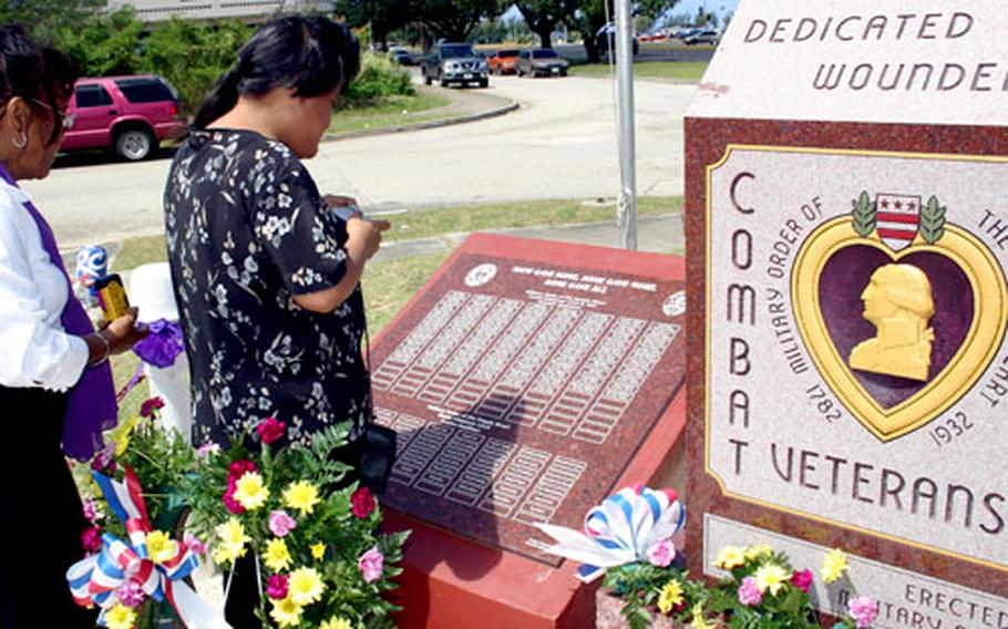 Deanna Payas, left, and her niece Teresita Gleason find the names of relatives on the just-dedicated Purple Heart Memorial in Hagatna, Guam.