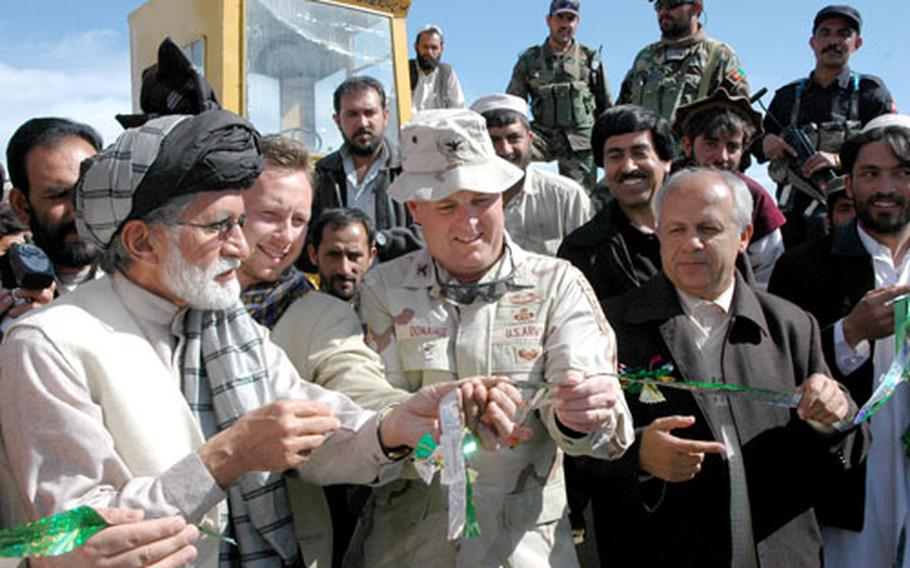 Governors Hakim Taniwal, left, and Merajuddin Patan flank Col. Pat Donahue during a ribbon-cutting ceremony marking the groundbreaking of a road that will connect the provincial capitals of Khowst and Gardez.
