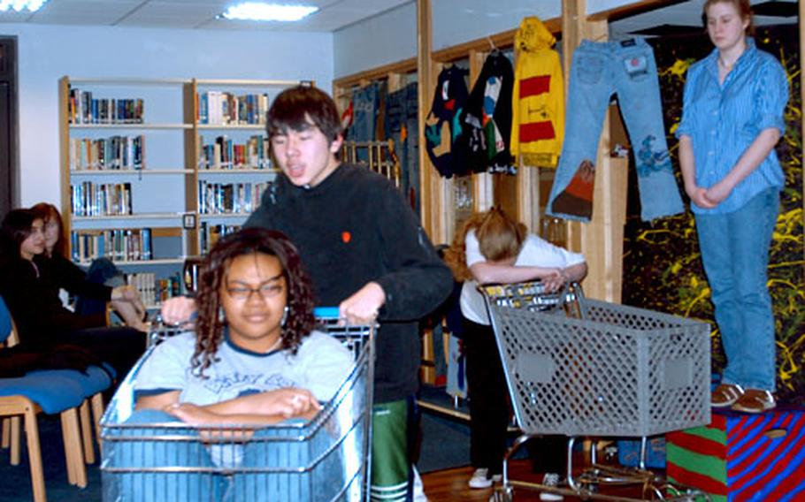 """Lloyd Kimpton pushes Amber Howard in a shopping cart during """"Fairy Tale: Wal-Mart!"""" Miranda Fluhrer, head down, and Bailey Lenart are in the background. The skit was part of the Lakenheath High School Drama Club production of """"Loadsa Laffs."""""""