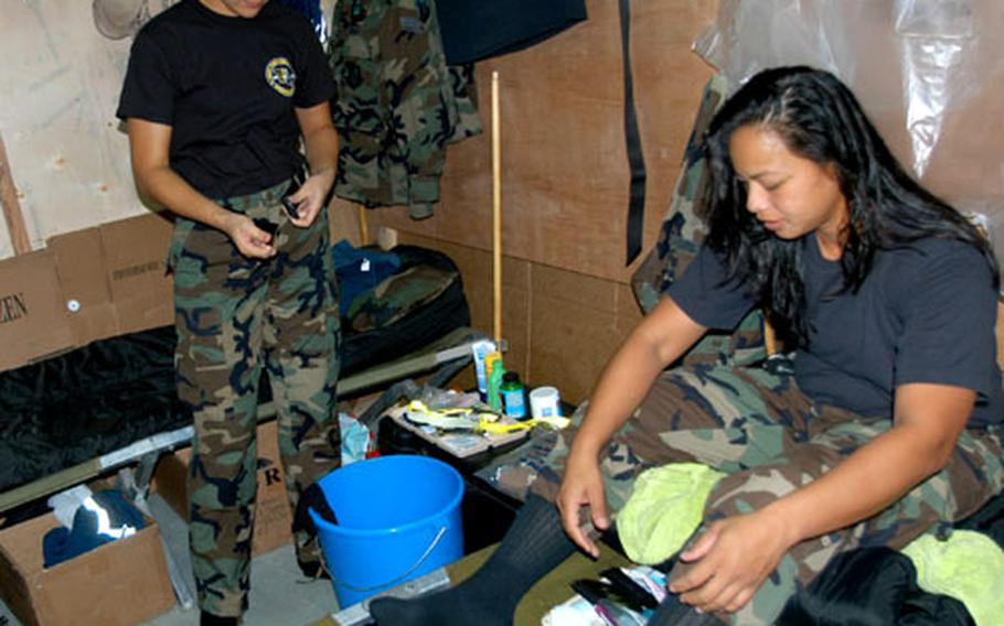 Senior Airman Denise Perez, left, and Staff Sgt. Rose Castro hang out Tuesday in their makeshift barracks at Fort Magsaysay, Philippines. The cooks from Guam International Guard's 254th Services Flight are among more than 400 soldiers roughing it at the Philippine army camp during the Balikatan exercise.